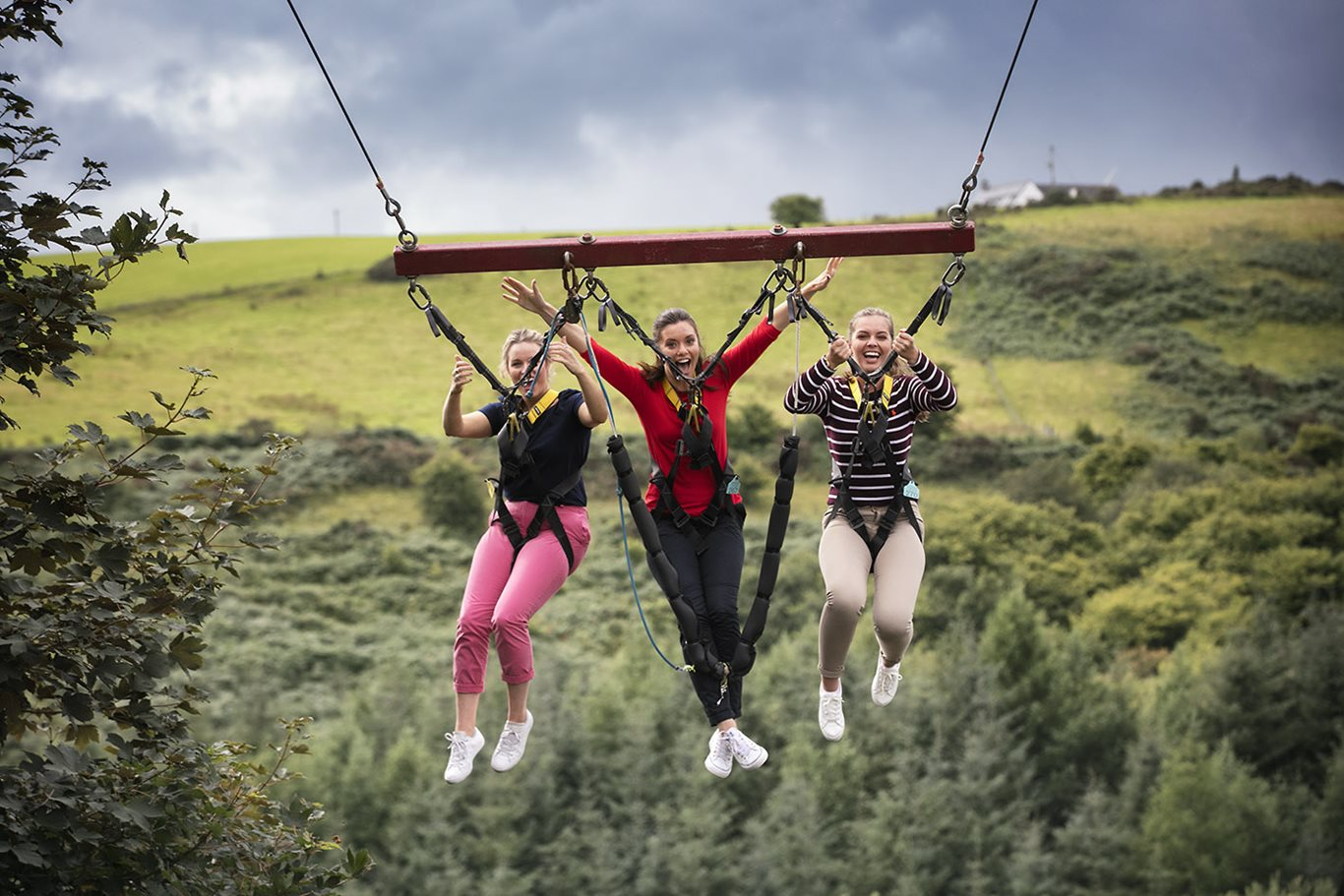 Three girls swinging through the air at Todds Leap